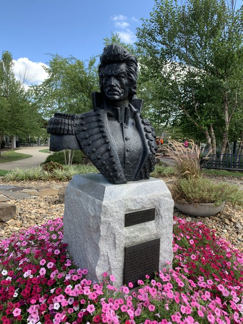 A bust of Revolutionary War hero Casmir Pulaski, for whom Pulaski County was named, rests on a stone pedestal surrounded by flowers in Little Rock's Riverfront Park.