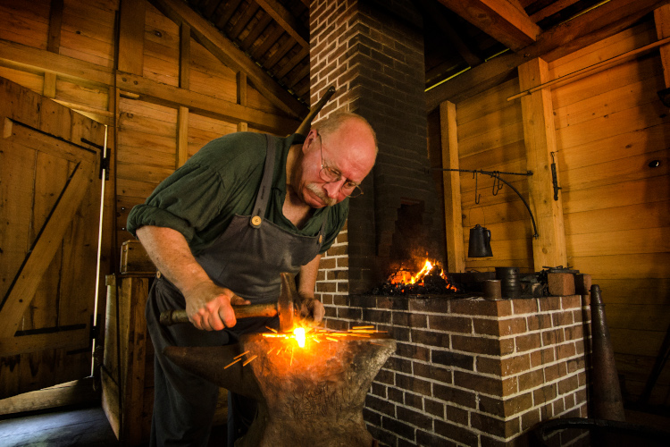 Historic Arkansas Museum-blacksmith hammers a horseshoe on an anvil