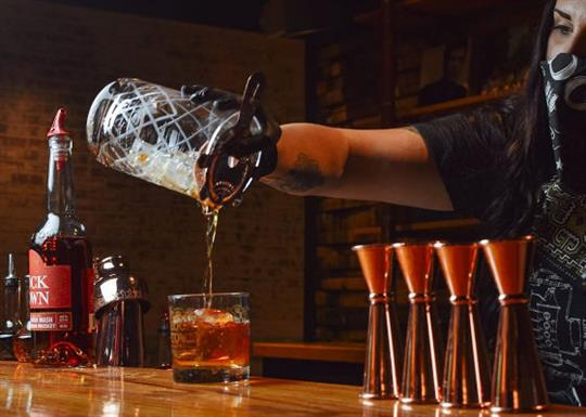 A bar tender pours whiskey in a glass in the Rock Town tasting room