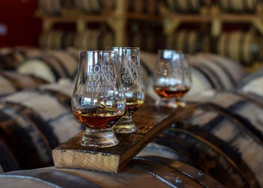 Four Rock Town snifter glasses sit on top of a charred oak board in the Rock Town aging room